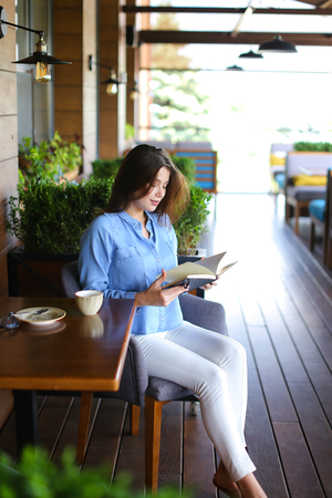 Pretty girl reading black diary at cafe   and shaking hair. Female person wears jeans shirt. Concept of resting at restaurant after lunch. Stock Photo