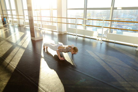 Engineer rock press in sport hall, male want to perfect body. Barefoot tattooed man in white trousers lie on parquet floor doing gymnastic exercises. Concept of individual training, well-equipped and light gym with nice atmosphere for workouts