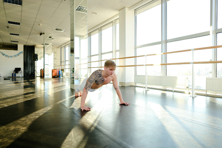 Model diligently rock press, tattooed guy try to keep fit. Handsome male with good body lie on floor in spacious well-equipped hall with big windows and mirrors. Concept of sportswear, gym for trainings or individual workouts Stock fotó