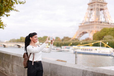 Smiling black-haired female taking pictures using smartphone. Concept of international education, changing of living place, cultural emigration Banque d'images
