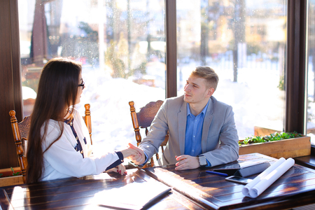 Young pretty secretary refusing business boss to touch hand at cafe with black document case on table. Handsome man wears grey suit and blue shirt. Concept of flirting with female worker at catering establishment.