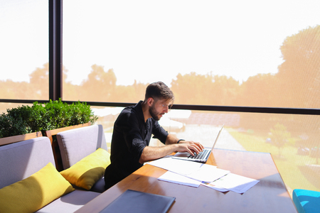 Tired quantity surveyor working at cafe table with diagram and statistic documents. Persistent man dressed in classic black shirt sitting at sofa near green indoor plants. Concept of  preparing estimates and costs of work, keeping track variations to contract affect costs and creating reports to show profitability. Stock Photo