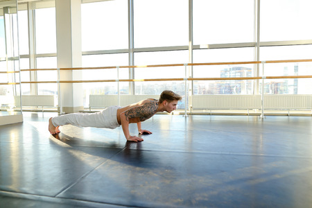 Interpreter doing press exercises in hall, young man fond of sports since childhood. Fair-haired tattooed guy in white trousers lie on parquet floor near ballet barre. Concept of sportswear, well-equipped gym for workouts or gymnastic school.
