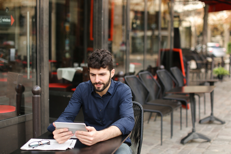 Dissatisfied man losing at online game playing with tablet at street cafe. Young man has dark hair, brown eyes and beard. Concept of excitement loss and Internet entertainments. Banco de Imagens