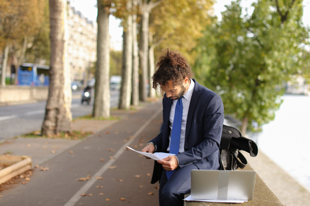 Young foreign boy planning study in France and reading instructions to exam candidates on laptop near Eiffel Tower.  Handsome Muslim guy sitting near river and dreaming. Attractive boy wears black suit and blue tie, has long curly hair and beard. Concept of entering to university and students exchange. Stock Photo