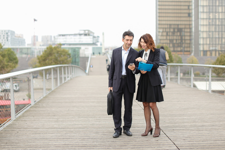 Middle-aged business man and woman classmates long time ago, accidentally met on street. Male show Female photo of family on smartphone and tell about wife with children. Female hold blue folder with paper, enthusiastically listen and smile. Stock Photo