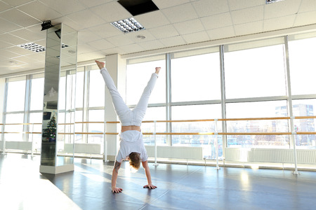 Male person making swipe and vigorous movements in white shirt and pants. Blonde dancer training at studio with large window and mirror. Concept of break dancing at gym. Stock Photo