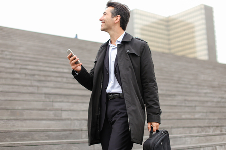 Business-style dressed man walking near city center. Male actively speaking by white smartphone looking around in different directions. Female gradually approaching to camera lens. Concept of business telephone speaking during walk.