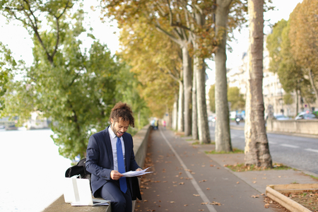 Young actor learning by heart new role for performance in Paris theatre with laptop near Eiffel Tower. Handsome man dressed in suit reading and gesticulating. Concept of preparing for speech on big scene. Banco de Imagens