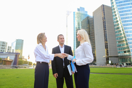 Business team members shaking hands in La Defense Paris,  . Concept of colleagues greeting and wishing good luck. Beautiful businesswomen talking with male partner.