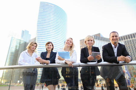 Beautiful businesswomen keeping blue document case talking with cheerful male boss outside. Concept of speaking with partners and joking about work. Pretty ladies dressed in white shirts smiling with man. Stock Photo