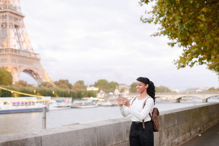 Blogger came to Paris for journey. Girl standing not far from Eiffel Tower and making video for social networks using gadget. Smiling young woman wearing white blouse and black trousers. Concept of shooting for vlog, international tourism, technology
