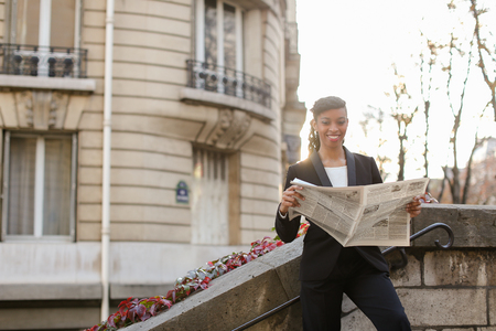 Pretty girl reading newspaper in open air with close up of face. Nice young lady dressed in classic style. Concept of taking rest with reading articles and working copywriter. Stock Photo