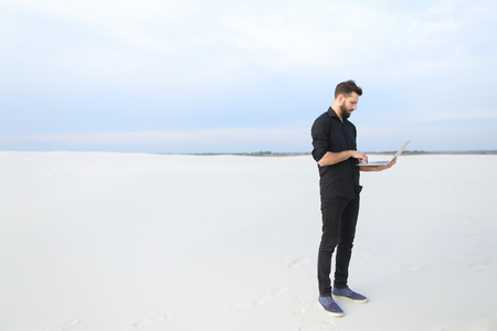 writer with laptop go to seaside, young man seek inspiration for book of travels. Stock Photo