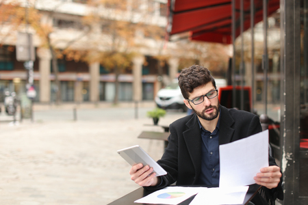 Businessman arguing, discussing project with partner by smartphone and reading papers at cafe table. Archivio Fotografico