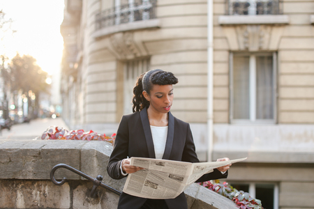 Young reporter looking at cam with newspaper on balcony near high building. Pretty woman looks successful and has ponytail hairstyle and black fleecy hair. Concept of working correspondent and writing articles. Stock Photo