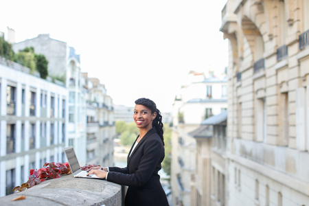 estate agent working with laptop on balcony near high building. Successful woman has ponytail hairstyle. Concept of apartments for rent, condos and home rentals.