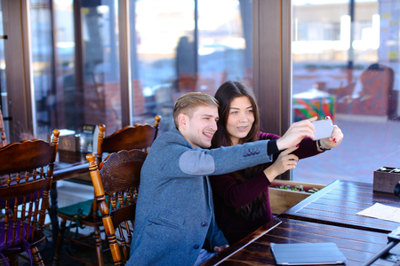 Bloggers taking selfie using smartphone in new luncheonette, boy with mustache and Asian girl visit cafe to make overview. Young people in formal clothes smiling making faces and showing tongue for camera. Concept of photography and innovative technologies, fashion or cozy coffee house with nice atmosphere