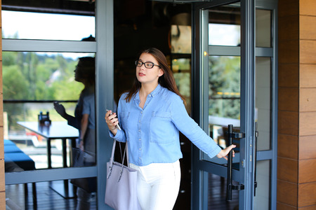 Cheerful female person leaving cafe, speaking by smartphone and stopping taxi. Young woman wears blue jeans shirt, white pants and glasses. Concept of satisfied customers and modern technologies.