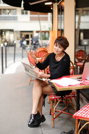 Woman sitting at table of street cafe skimmed through new newspaper. Female with short haircut dressed in black dress gestures  shares emotions with interlocutor. Lady smiling and looks wondering. Concept of involvement in news. Stock Photo