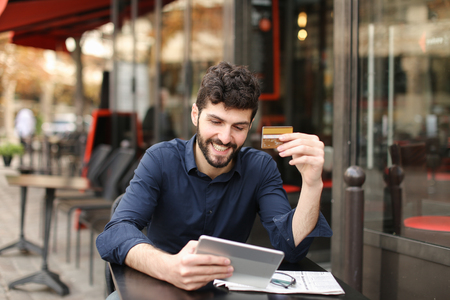 Gladden prosperous man purchasing at online shop with money card and tablet with close up face in  . Satisfied man sitting at street cafe and smiling. Concept of buying goods using Internet.