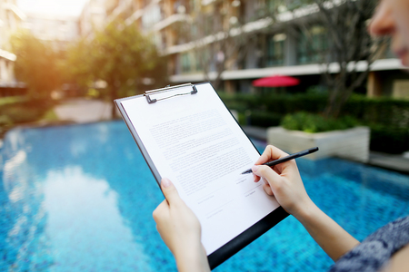 Close-up of girl hand and document on background of sunny day pool. woman signs lease on housing or real estate. concept of contract between people, travel. Front used with Open Font License