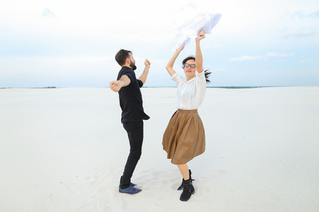 future lawyers male and female come to seaside to have rest after passing exams, girl with ponytail in glasses tell good news friend bearded man with short fair hair. Archivio Fotografico