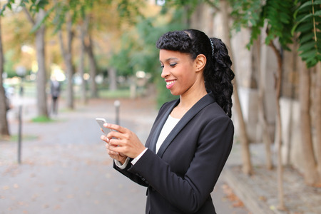 Travel agent talking on smartphone with client and advising cheap tours in park.