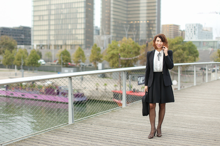 journalist talking on smartphone, woman in business clothes go to work. Smiling middle-aged American lady wearing black jacket skirt and white blouse talking with friend on mobile. Stock Photo
