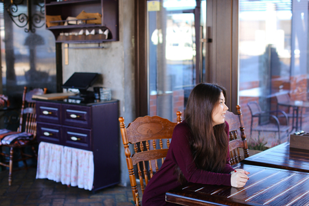 Model waiting photographer for photoshoot in cafe, Asian smiling girl sitting near wooden table. Young woman with long hair and neat red manicure wearing dress looking around.