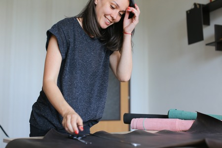 teacher demonstrating future seamstresses how to work with leather, young woman teaching to make bags. Female with red nails wearing grey T-shirt standing near table in workshop and preparing to cut necessary pattern.