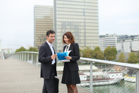 Middle aged european appearance man and asian young woman standing on place, new project build. Smiling partners discuss last details with enthusiasm and eventually shake hands.
