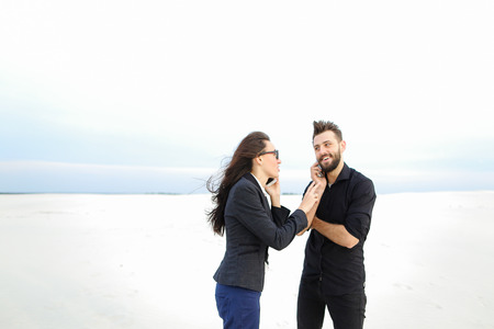 models man and woman come to seaside for photoshoot, young people jumping for joy among sands. Bearded guy wearing black shirt trousers and fair-haired lady in suit have good mood embrace. Concept of photosession, fashionable clothes or stylish outfits.