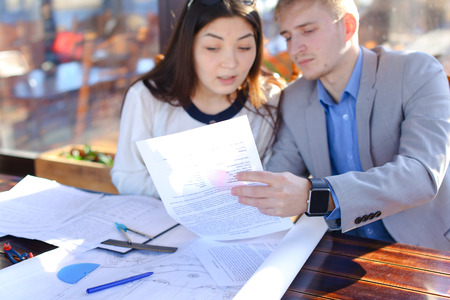 Students of architectural faculty calling to teacher to ask about architectural project. Guy and girl drafting at cafe. Concept of work in pair and drawing course work. Stockfoto