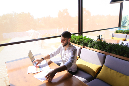 Lucky successful manager working with laptop and documents with diagrams at table indoors. Young gladden man enjoying good job and result, looking at cam and gesticulating yes. Concept of prosperous high class professionals and using modern devices for Internet. Banco de Imagens
