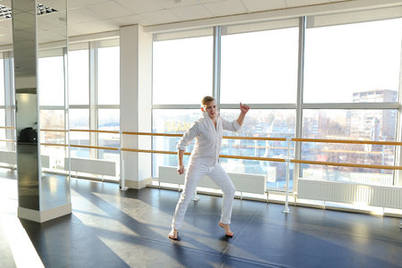 Winner of dancing competition training at spacious studio near mirrors . Young blonde boy moving for warming up muscles. Concept of doing exercises for being in good shape. Stock Photo