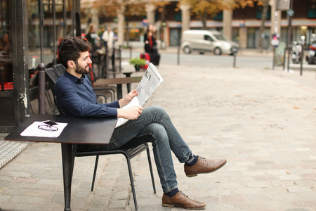 Happy male person enjoying reading newspaper at cafe in  . Glasses and smartphone put on table. Concept of public press information and resting. Archivio Fotografico