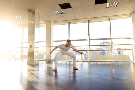 Master of sport in gymnastics come to gym for training on weekend, boy with good body warming up. Tattooed guy standing not far from ballet barre waving hands sloping. Concept of man sportswear, big gym or individual workouts.