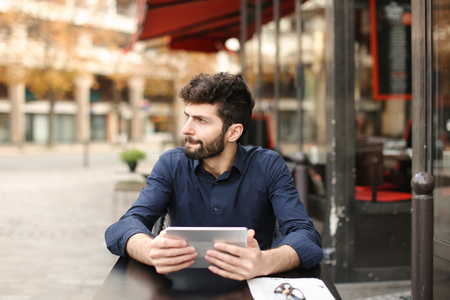 Dissatisfied man losing at online game playing with tablet at street cafe. Young man has dark hair, brown eyes and beard. Concept of excitement loss and Internet entertainments. Imagens