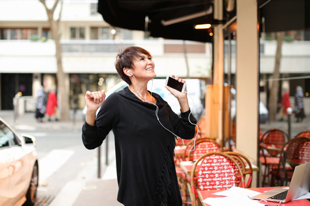 middle-aged woman tourist standing near Italian cafe and listen music in smartphone by earphones. Pretty lady with short haircut have good mood and dancing to music. Female shaking hands swinging from side to side, sing along. Concept of listening music in all place with modern gadgets. Stock Photo