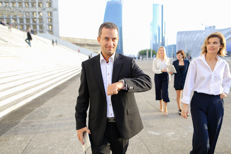 Employees of financial organization walking in   with tablet and document cases in  . Concept of prosperous team members and time management. Successful people wears business clothes. Reklamní fotografie