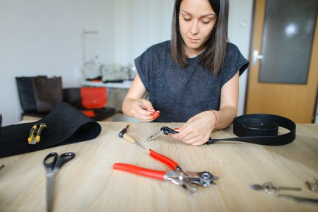 female fixing snap on leather pattern using special mechanism. Young designer decided to try to make women bags for sale. Black-haired girl with red nails wearing grey T-shirt sitting near table in workshop. Concept of creative work, own business or handwork. Stock Photo