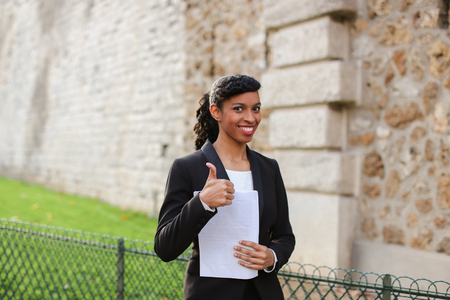 Half Nigerian girl reading exam result papers in open air. Young gladden color female person has good mood and charming smile. Stock Photo