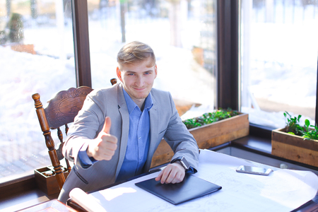 Happy young businessman speaking by smartphone at cafe with roll architect project on table.