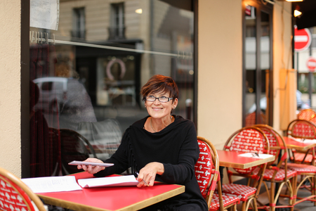 Business woman sitting at table in street cafe, fill declaration with tablet and sheets of paper.