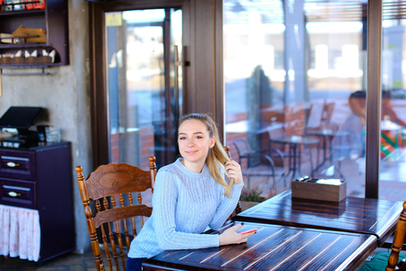Model waiting photographer for photoshoot in cafe, Asian smiling girl sitting near wooden table. coffee house, quite place for rest or beautiful furniture in luncheonette. Stock Photo