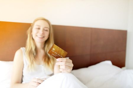 focus on credit card, holding by young american woman in white bed. concept of online banking, funds or currency exchange sending payments with sunshine
