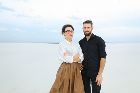 Student male develop project of cafe at seaside and agree with business woman on buying plot of land, people viewing documents. Bearded guy smiling shaking hands with fair-haired lady with earrings. Concept of property for sale, beach arrangement or negotiations and meetings.