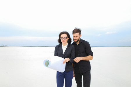 CEO male and CFO female holding whatman paper, colleagues discuss project of wind power plant in deserted place.
