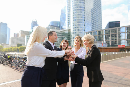 Prosperous business team rejoicing good result and greeting each other outdoors in  . Concept of enjoying win tender and employees of large organization. Happy satisfied partners smiling and greeting each other. Stock Photo
